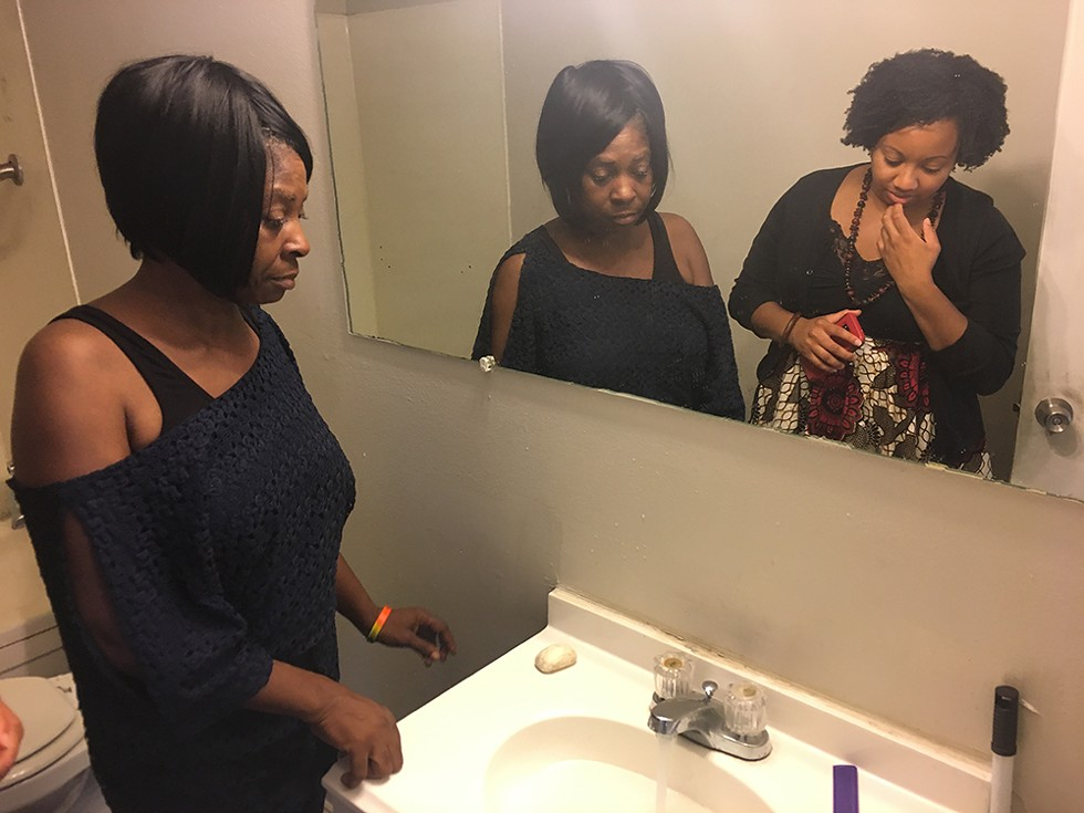 Lillie McGee runs her faucet for Amina Kirk, a legal advocate with the Detroit People's Platform, to show that her hot water doesn't work. - VIOLET IKONOMOVA