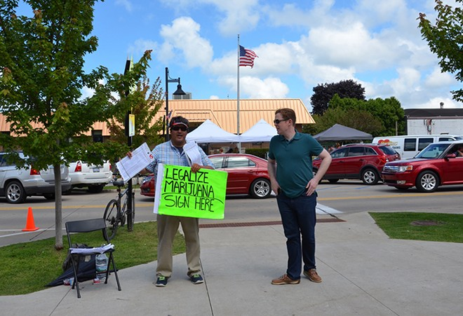 An activist encourages visitors to the National Blueberry Festival in downtown South Haven to sign a petition to legalize marijuana in Michigan. - SUSAN MONTGOMERY