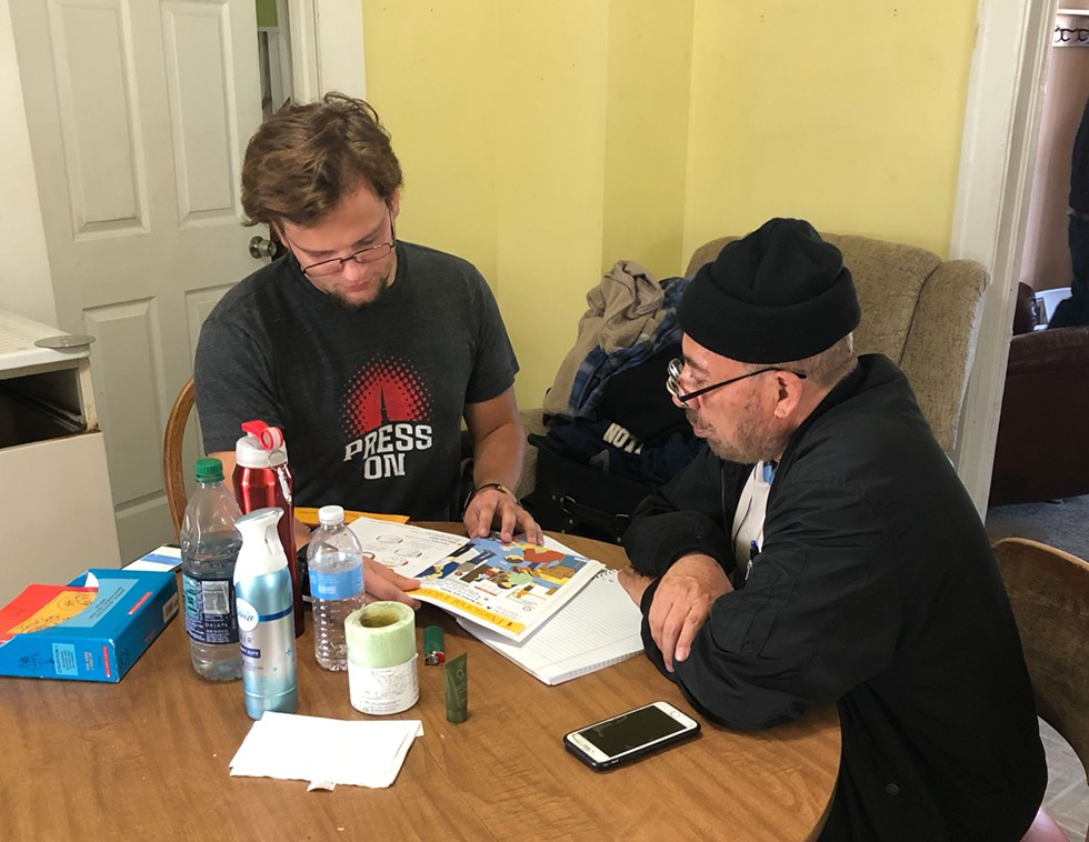 Caleb teaching a man English at Kirby's Hamtramck home. - SAMUEL COREY
