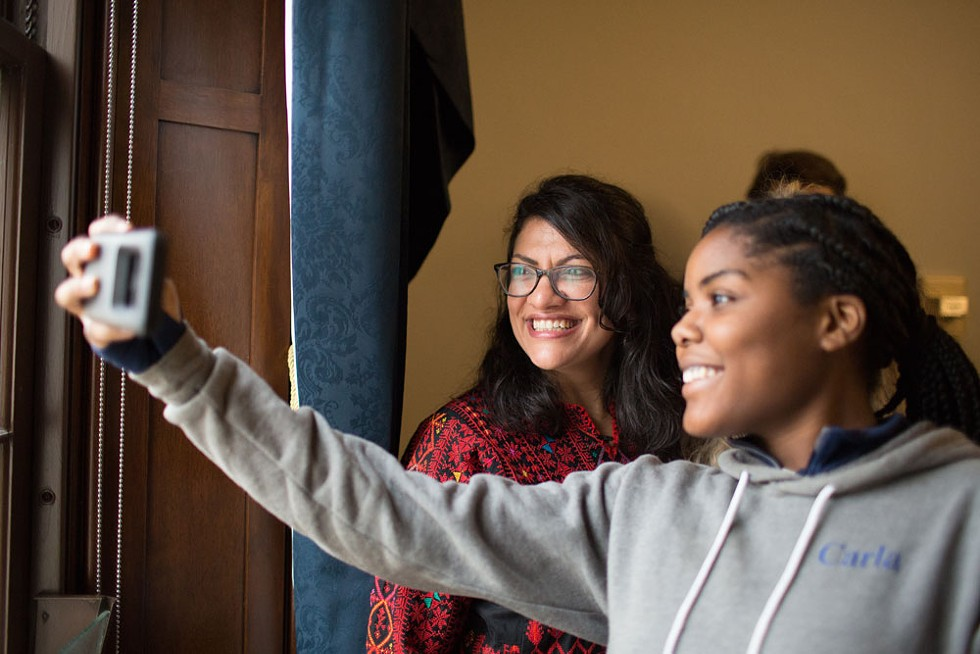 """Teenager Carla Underwood, who volunteered for Tlaib's campaign, poses for a selfie with the new congresswoman. She says she sees herself in her newly elected representative. """"I always thought this was so far away from me. Untouchable,"""" she says. """"The government was far away and separate from my life here in Detroit. In many cases, people aren't represented like they should be represented. Rashida gives me hope that I can do this too if I wanted to. I always thought of this as a 'them' thing. Not something that someone like us from Detroit could achieve."""" - ERIK PAUL HOWARD"""