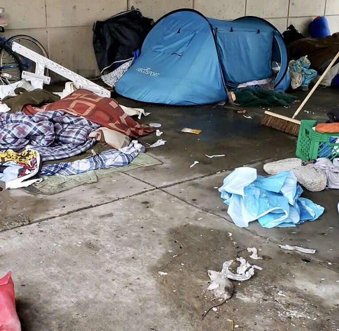 A dead rat is among the belongings in a homeless camping spot under an overpass. - COURTESY OF CITY OF DETROIT