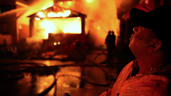 Detroit Fire Department's FEO Dave Parnell stands outside a burning home. - BURN FILM