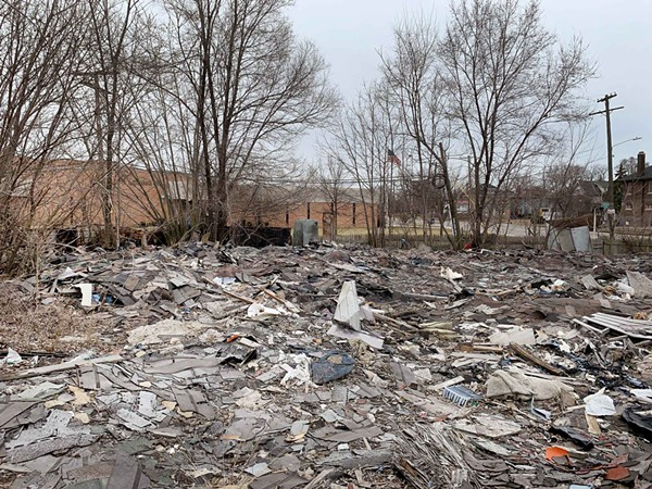 Illegal junkyard pictured with an elementary school in the background. - TOM PERKINS
