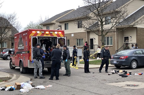 Medics place the shooting victim in an ambulance at the Brewster housing complex. - STEVE NEAVLING