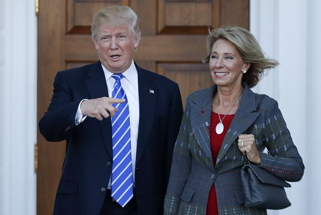 Betsy DeVos and her boss, an accused sexual predator. - SHUTTERSTOCK