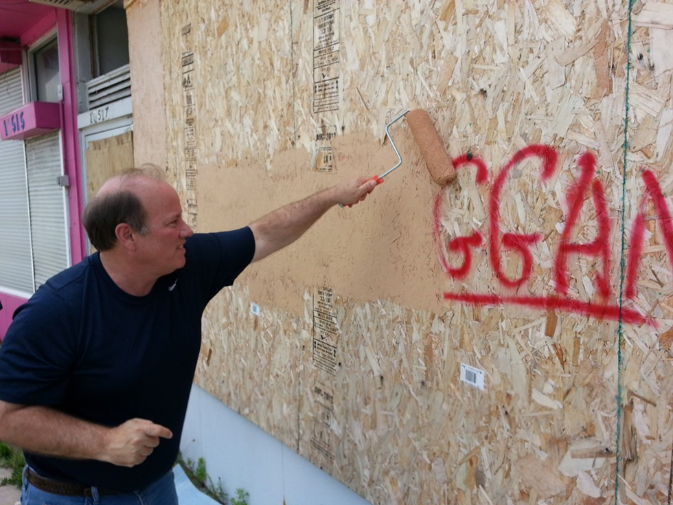 Detroit Mayor Mike Duggan buffs graffiti bearing his name in 2013. - JON HEWETT/WWJ