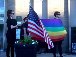A rainbow pride flag flies next to the American flag at a Sunday vigil in Ferndale for victims of a mass shooting at a gay nightclub in Orlando that left 50 dead. - PHOTO BY DUSTIN BLITCHOK