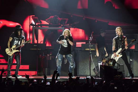 """Duff McKagan, left, Axl Rose, and Slash at the """"Not In This Lifetime..."""" tour opener at Ford Field in Detroit on Thursday. - PHOTO BY MIKE FERDINANDE"""