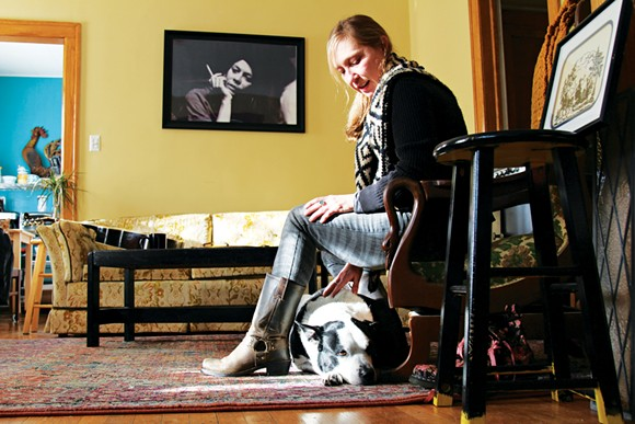 Alison Lewis relaxes with her cattle-dog mix Millie, who survived getting shot in the face by a police officer in 2015. - PHOTO BY SARAH RAHAL.