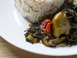 Molokhia (jute leaf) with red palm oil and pepper served with jasmine rice. - PHOTO BY JACOB LEWKOW.