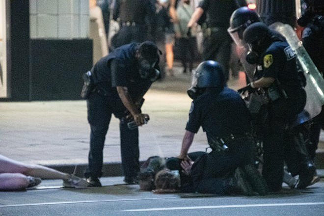 Detroit police pepper-spray a protester in the face while he's being held down. - ADAM J. DEWEY