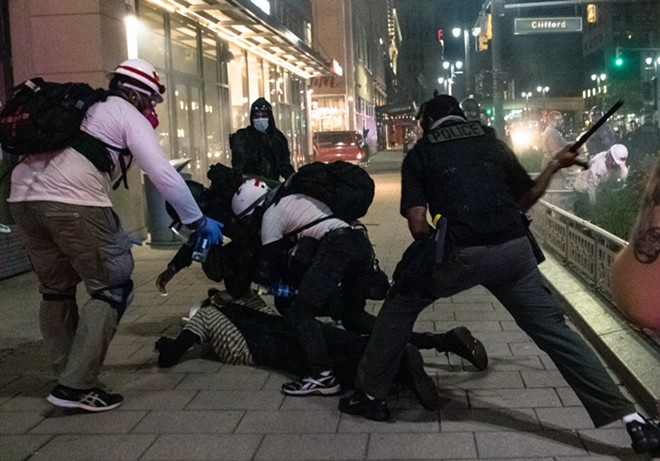Police use a baton during an Aug. 23 protest in Detroit. - ATTORNEYS FOR DETROIT WILL BREATHE