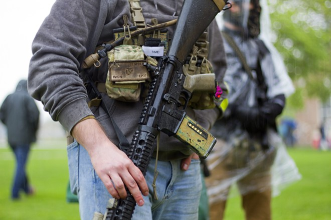 Armed protesters rallied against Gov. Gretchen Whitmer's coronavirus restrictions in May. - STEVE NEAVLING