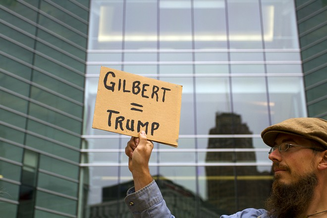A protester holds up a sign at an August 2017 rally against a Donald Trump fundraiser in a Dan Gilbert building. - STEVE NEAVLING