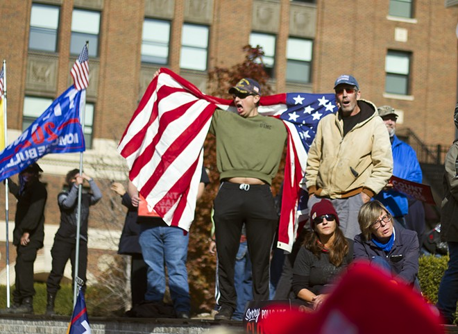 Michael Joseph Foy draped in an American flag at a pro-Trump rally in Detroit in November. - STEVE NEAVLING