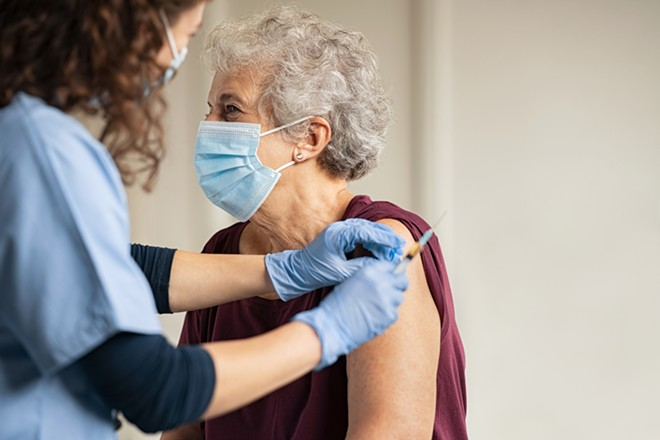 Doctor giving injection to senior woman at hospital. - SHUTTERSTOCK
