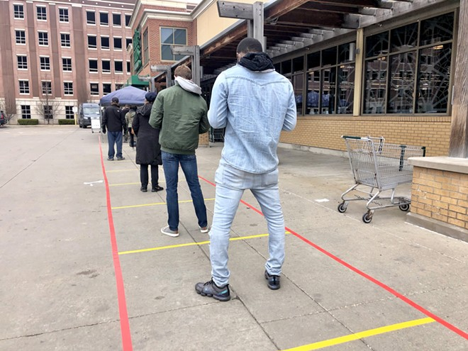 Social distancing markers guide an overflow line outside the Detroit Whole Foods store. - STEVE NEAVLING