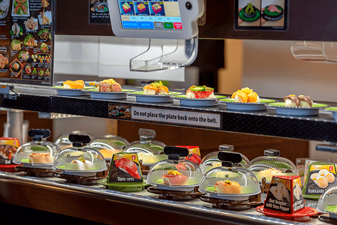 A conveyor belt delivers plates of sushito customers. - COURTESY OF KURA SUSHI