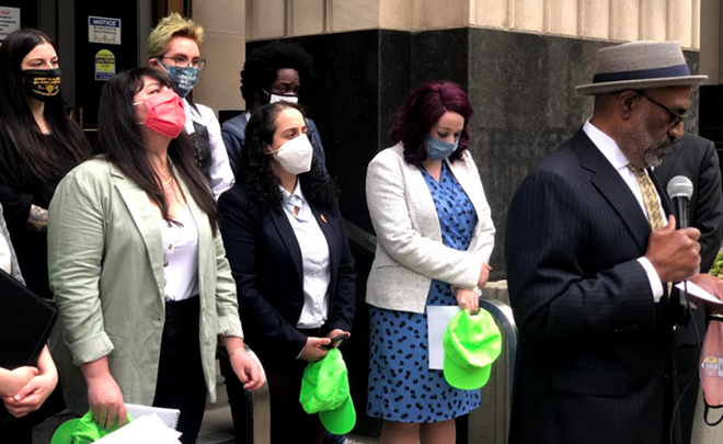 Attorney David Robinson, right, is representing five legal observers from the National Lawyers Guild, holding their signature neon green hats, who say they were brutalized by Detroit police last summer. - JACK W. SCHULZ