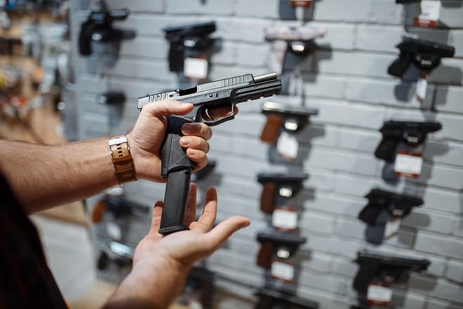 Man choosing new handgun in gun shop. - SHUTTERSTOCK