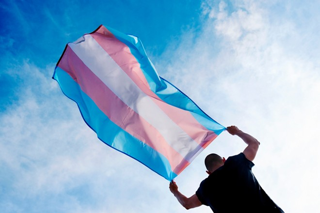 A person holding a transgender pride flag. - SHUTTERSTOCK