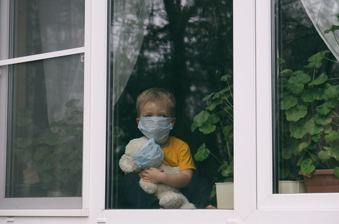 Sad child in protective medical masks looks out the window. - SHUTTERSTOCK