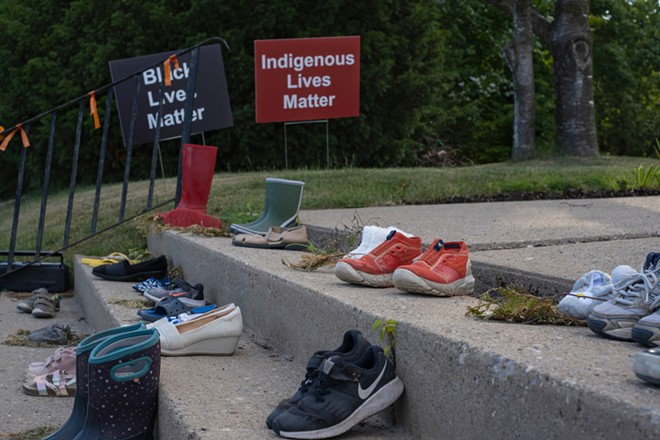 Shoes and toys at a memorial by a Catholic church in Toronto in tribute to 215 indigenous children whose remains were found in a school in Kamloops, British Columbia. - ELENA BERD / SHUTTERSTOCK.COM