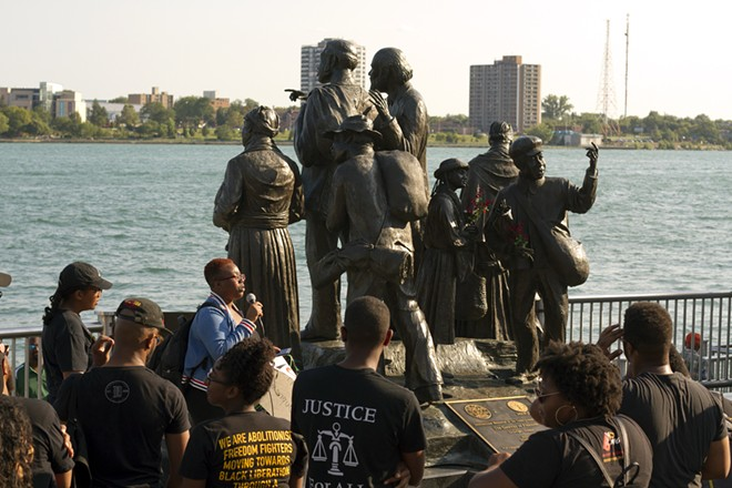 Black activists rally against racism next to an Underground Railroad monument in Hart Plaza in Detroit. - STEVE NEAVLING
