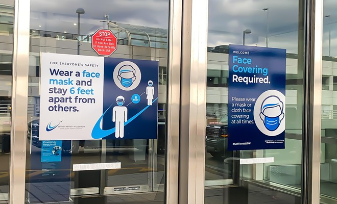 Entrance door of DTW terminal building with sign requiring masks. - GG5795 / SHUTTERSTOCK.COM
