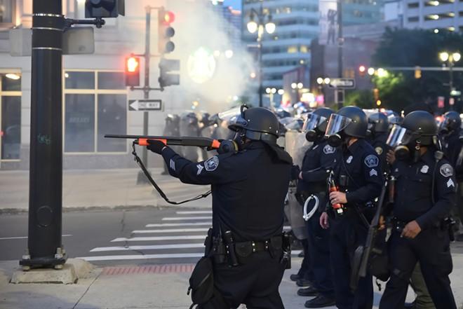 Detroit cop fires at protesters. - LESTER GRAHAM / SHUTTERSTOCK.COM