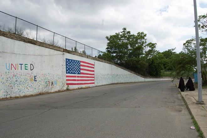 Muslim women walking near an American flag mural in Hamtramck, Michigan. - LEE DEVITO