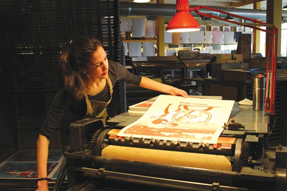 Sophia Pappas prints her poster for Power of the Press Fest at Eastern Market's Signal-Return. - SARAH RAHAL