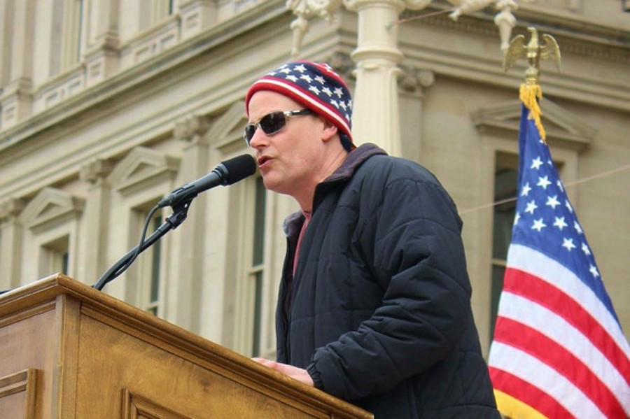 """MI Legalize board member Jamie Lowell addresses a crowd at the State Capitol during a 2015 """"Stop the Raids"""" rally in response to police raids of homes and businesses of medical marijuana patients and caregivers. - COURTESY PHOTO"""