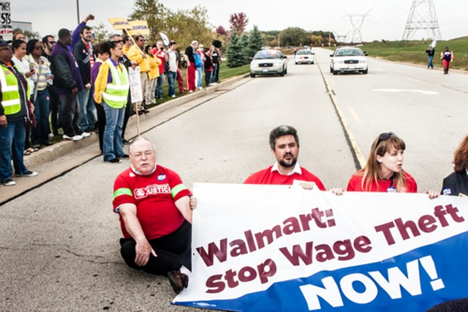 Wage theft protesters stage a sit-down protest to block the entrance of the Walmart distribution center in Elwood, Ill. - PHOTO COURTESY SHUTTERSTOCK