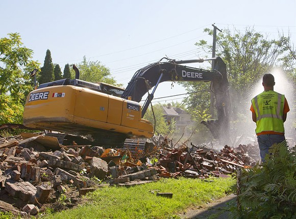 The Detroit Land Bank knocks down a dilapidated house on the city's west side in September 2015, when Detroit averaged 150 demolitions a week. - STEVE NEAVLING