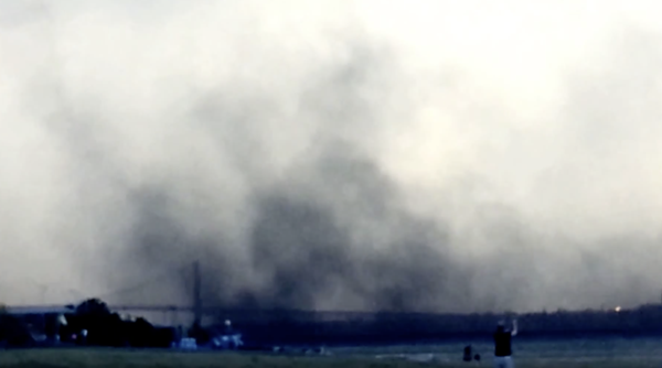 Airborne particles from petcoke piles along the Detroit River swirl above the Ambassador Bridge in 2013. - SCREENGRAB, YOUTUBE