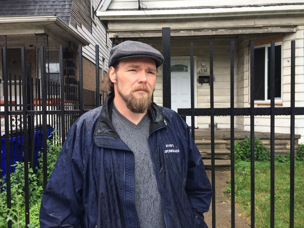 Joseph Bates, 48, stands in front of the Southwest Detroit home his great-great-grandparents bought in 1907. The home had been in his family until it was foreclosed due to unpaid tax bills. - VIOLET IKONOMOVA