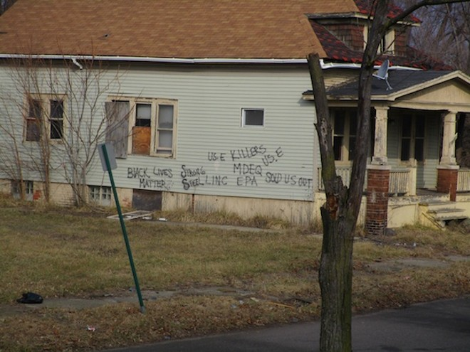 """A house on Concord Avenue, a block-and-a-half away from U.S. Ecology, bears complaints about the nearby toxic waste facility: """"US. E KILLERS ... MDEQ SOLD US OUT."""" - PHOTO BY MICHAEL JACKMAN"""