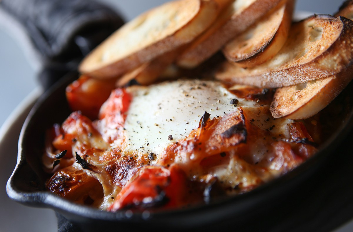 Tomatoes in Cast Iron, heirloom tomatoes, sofrito, egg, cheese curd, and baguette, from Lucy & the Wolf in Northville.