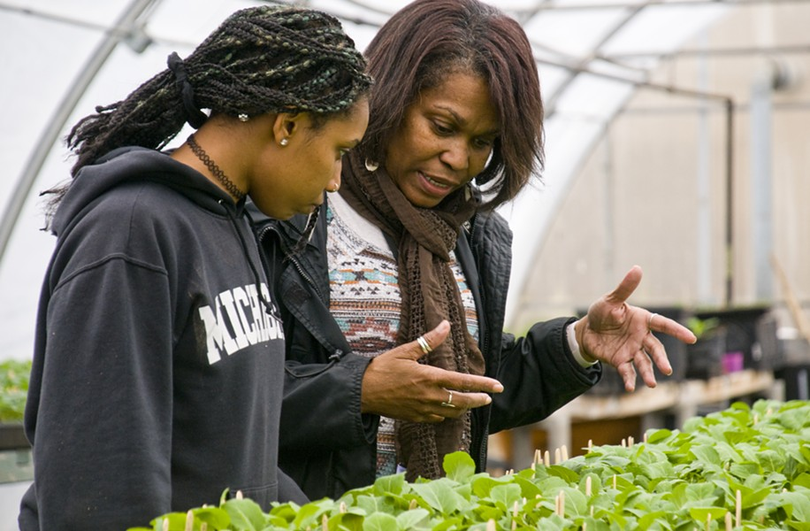 Nefer Ra Barber working with a student in a hoophouse that's used for the EAT program at Earthworks program. - TOM PERKINS