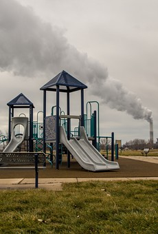 Playground in William C. Sterling State Park with billowing smokestack in the background.