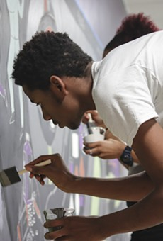 A student at Detroit's Southeastern High School, where there is no formal art program, paints a mural as part of a new partnership between the school and the Heidelberg Project.