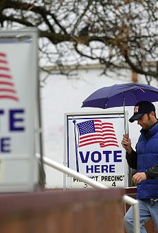 A man walks into a precinct on a rainy election day, his umbrella broken.