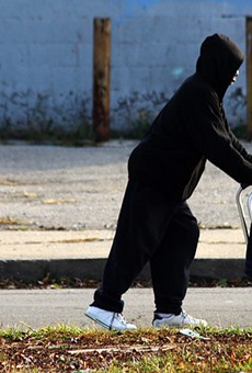 A man pushes a walker down Peterboro Street in Detroit.