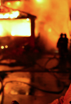 Detroit Fire Department's FEO Dave Parnell stands outside a burning home.