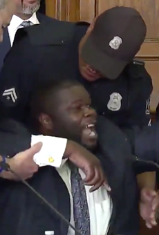 Detroit police yank police commissioner Willie Burton from his seat.