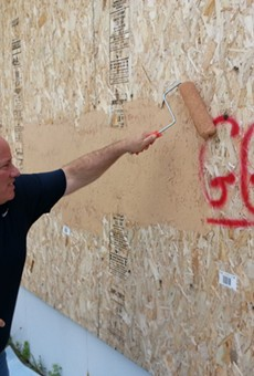 Detroit Mayor Mike Duggan buffs graffiti bearing his name in 2013.