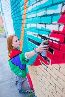 Ellen Rutt preps a wall for Murals in the Market.