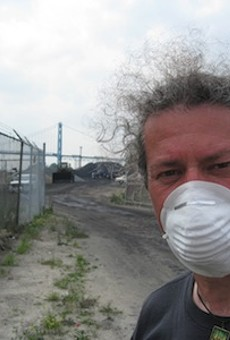 A protester stands in front of the piles of petcoke that graced the riverfront in 2013. The piles have since been removed.