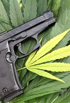 On the federal level, marijuana is still illegal, and it's a felony punishable by up to 10 years in prison to smoke pot and buy or own a gun.